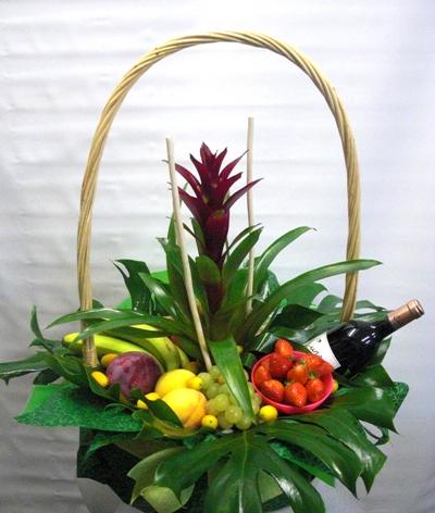 Cesta de frutas con vino y plantas naturales