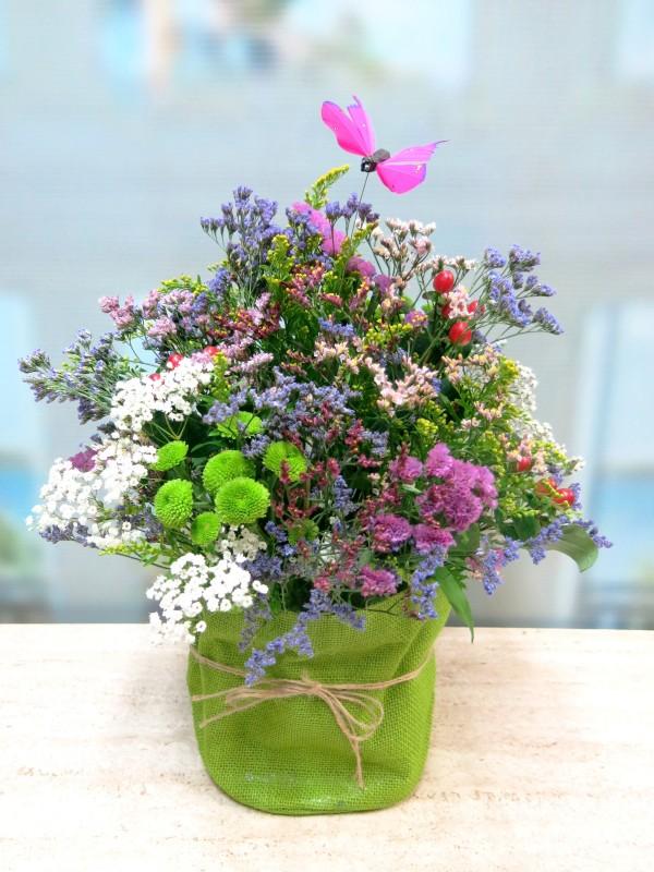Centro de flores vintage en recipiente de tela