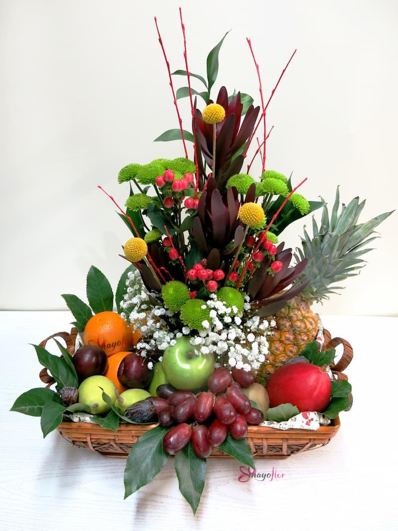 Frutas variadas y flores en un centro panera - Foto principal